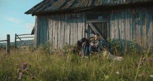 Halny kraj lovestory 4K Mężczyzna i kobieta siedzi na ganeczku z ich dwa psami cieszymy się wieczór światła - Robi bermann zbiory