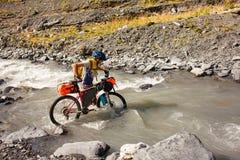 Halny rowerzysta krzyżuje rzekę w średniogórzach Tusheti Fotografia Royalty Free