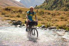 Halny rowerzysta krzyżuje rzekę w średniogórzach Tusheti Zdjęcie Stock