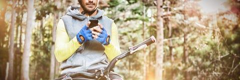 Halny rowerzysta używa telefon komórkowego zdjęcia stock
