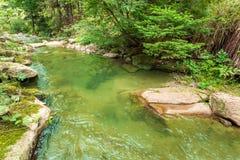 Halny strumienia spływanie między kamieniami Zdjęcie Royalty Free