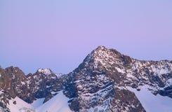 Halny szczyt w śniegu nad purpurowym zmierzchu niebem Obraz Stock