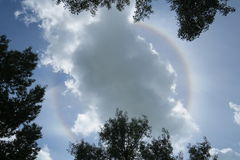 Halo around a cloud that hides the sun. Sun's halo piercing through a cloud in a bright and peaceful day royalty free stock photography