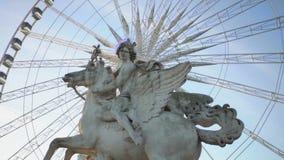 Halo de la iluminación alrededor de la estatua ecuestre de Pegaso de la rueda grande que trabaja detrás almacen de video