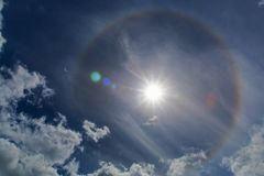 Halo Sun Ring. Halos are atmospheric phenomena created by light which is reflected or refracted by ice crystals in the atmosphere. Halos can have many forms stock photo