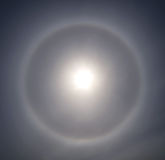 Halo and sun in the sky clouds and a thin layer of cirrus clouds. Halo and sun in the sky clouds and a thin layer of cirrus clouds stock photo