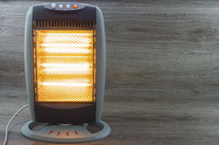 Halogen Electric Stove. Illuminated and radiating on gray background stock images