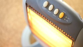 Halogen Infrared heater being turned on and off. With focus on finger pressing the power button. Concept for heating, heat, cold, winter, household, appliance stock video footage