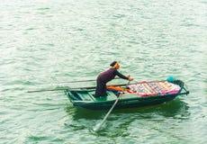 HALONG, ΒΙΕΤΝΆΜ - 16 ΔΕΚΕΜΒΡΊΟΥ 2016: Μια γυναίκα σε μια βάρκα με τα τρόφιμα Διάστημα αντιγράφων για το κείμενο Στοκ φωτογραφία με δικαίωμα ελεύθερης χρήσης