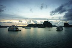 Halong bay at sunset with tourist cruise ships and rocky islands. Popular landmark, famous destination of Vietnam.  stock image