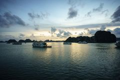 Halong bay at sunset with tourist cruise ships and rocky islands. Popular landmark, famous destination of Vietnam.  royalty free stock photography