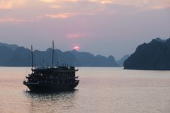Halong Bay at sunset, Vietnam. View of the UNESCO world heritage site Halong Bay in the north east of Vietnam. In the front you can see an old style cruise ships Stock Photography