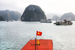Halong Bay, Vietnam Landscapes, Vietnamese Flag in the foreground and signature Limestone Island in the Background Royalty Free Stock Photography