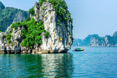 HALONG BAY, VIETNAM - SEPTEMBER 24, 2014 - A fishing boat of the local fishermen going nearby a mountain in the Bay Stock Photo