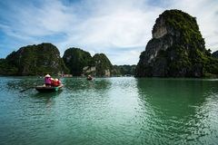Halong bay in Vietnam, UNESCO World Heritage Site, with tourist rowing boats Stock Photos