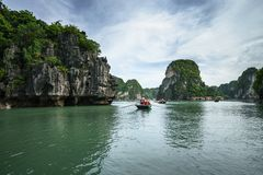 Halong bay in Vietnam, UNESCO World Heritage Site, with tourist rowing boats Stock Image