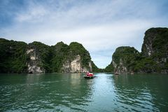 Halong bay in Vietnam, UNESCO World Heritage Site, with tourist rowing boats Royalty Free Stock Photography