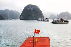 Halong fjärd, Vietnam landskap, vietnamesisk flagga i förgrunden och häftekalkstenö i bakgrunden Royaltyfri Fotografi