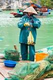 HALONG VIETNAM - DECEMBER 16, 2016: En kvinna i fjärdförsäljningsfisken vertikalt Kopiera utrymme för text Royaltyfri Bild