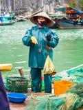 HALONG VIETNAM - DECEMBER 16, 2016: En kvinna i fjärdförsäljningsfisken vertikalt Kopiera utrymme för text Arkivfoton