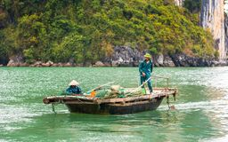 HALONG, VIETNAM - DECEMBER 16, 2016: Fisherman in a boat in the Halong bay. Copy space for text. Royalty Free Stock Photography