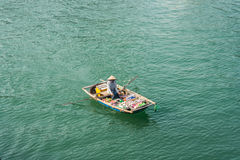 HALONG, VIETNAM - OCTOBER 11, 2016: Vietnamese saleswoman from b. Oat on the water Royalty Free Stock Images