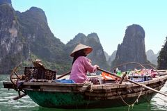 Halong, Vietnam - OCTOBER 30, 2011: A woman is selling food on a boat in the floating village of Kua Wan near the island of Daw Gu royalty free stock photo