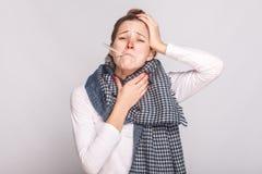 Hals och huvud för ung sjuk kvinna hållande Ha en temperatur arkivfoton