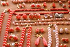 Halsband, örhängen och dyrbara ädelstenar i en ställning arkivbilder