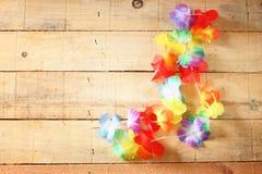 Halsband av ljusa färgrika blommalei på wood bakgrund fotografering för bildbyråer