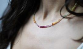 Halsband av m?ngf?rgade och skinande stenar p? halsen av en ung kvinna royaltyfri bild