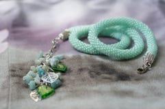 Halsband av mintkaramellfärg på en textilbakgrund royaltyfri bild