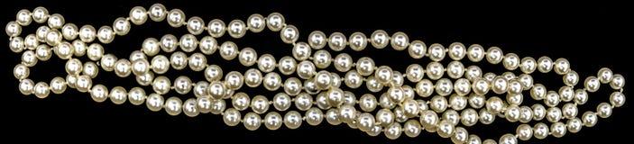Halsband av pärlor, i hög upplösning i landskapformatet som isoleras från svart bakgrund, som baner eller titelraden för en blogg Arkivfoton