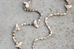 Halsband av snäckskal på en grå bakgrund Royaltyfri Foto