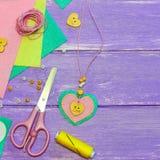 Halsband för hjärta för valentindagfilt Halsband för dag för valentin` som s göras av filt, pärlor och en träknapp Hantverktillfö Royaltyfria Foton
