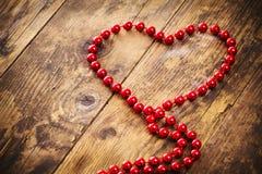 Halsband för hjärtaformpärla, en träbakgrund. royaltyfri foto