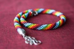 Halsband från mång--färgade pärlor på en textilbakgrund arkivfoto