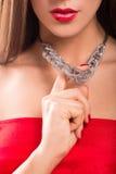 Halsband på kvinnlig hals Flickainnehavhänder rött sexigt för kanter royaltyfri foto