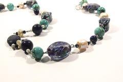 Halsband som göras av naturliga lasursten-, turkos- och exponeringsglaspärlor på en vit bakgrund royaltyfri bild