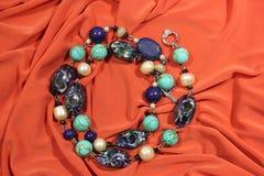 Halsband van natuurlijke halfedelstenen wordt gemaakt - lapis lazuli, turkooise en witte rivierparels op een roze achtergrond die stock afbeelding