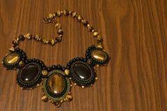 Halsbandet av handgjorda pärlor och det naturliga stentigerögat av brunt och agat svärtar på en träbakgrund Arkivbilder