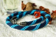 Halsbandet från blått pryder med pärlor på en textilbakgrund Royaltyfri Foto