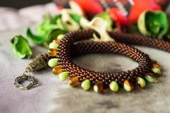 Halsbandet från brunt pryder med pärlor och pryder med pärlor i form av droppar Royaltyfria Bilder