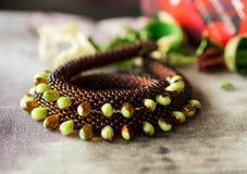 Halsbandet från brunt pryder med pärlor och pryder med pärlor i form av droppar på en textilbakgrund Royaltyfri Fotografi