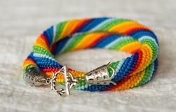 Halsbandet från pärlor av en regnbåge färgar på en textilbakgrund Arkivfoto