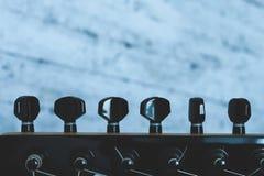 Halsen av gitarren och det svarta instrumentet som trimmar apparaten fotografering för bildbyråer