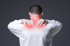 Halsen smärtar, man med ryggvärk på grå bakgrund arkivfoton
