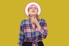 Halsen sm?rtar sjukdom eller influensa St?ende av den sjuka moderna stilfulla mogna kvinnan i tillf?llig stil med hatt- och glas? royaltyfri bild