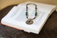 Halskette, die auf das Buch legt Lizenzfreies Stockbild