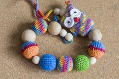 Halskette gemacht von gestrickten Perlen und von Spielwaren für das Baby, das in einem Riemen sitzt Riemenhalskette stockfotos